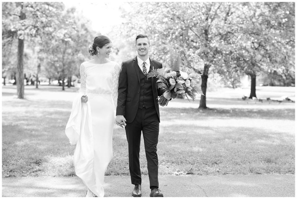 A photograph in black and white of the bride and groom smiling and walking together as they hold hands at Dock 580 wedding venue in downtown Columbus by Alayna Parker Photography  - Columbus OH wedding photographers