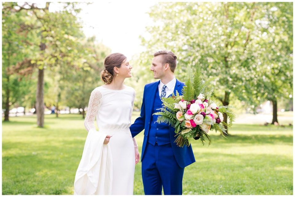 A photograph of a bride and groom pausing in a park, romantically smiling at each other at Dock 580 wedding venue  by Alayna Parker  - Columbus OH wedding images