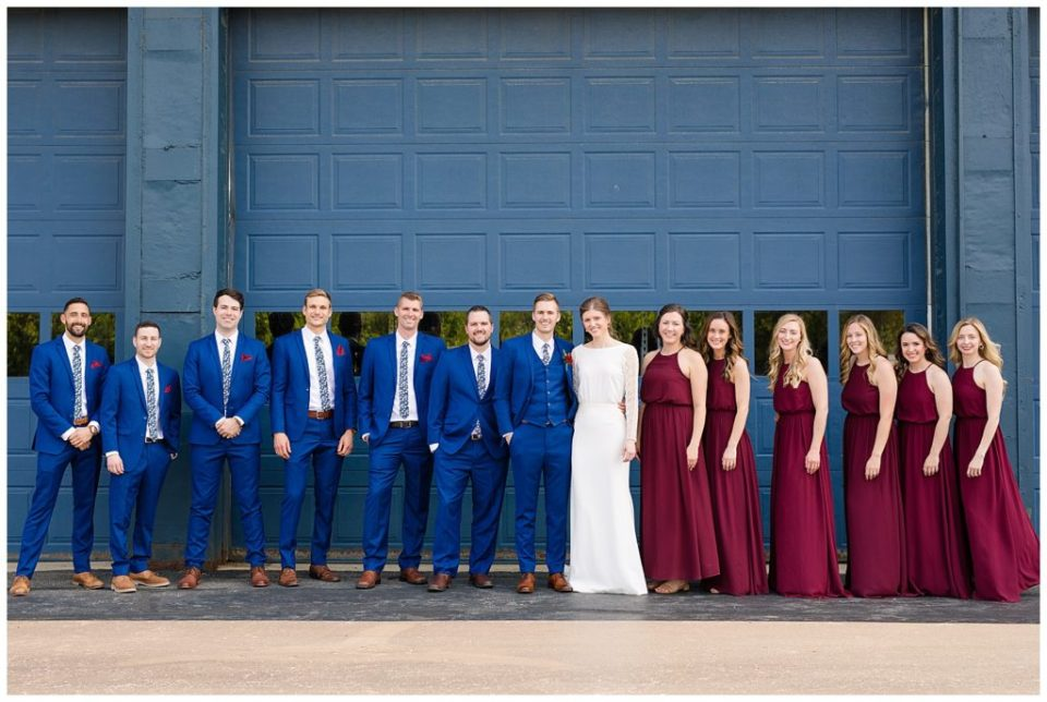 An image of a bride and groom standing with their wedding party lined up and smiling at Dock 580, in the hostoric Smith Bros Hardware building by Alayna Parker  - Columbus Ohio marriage photographer