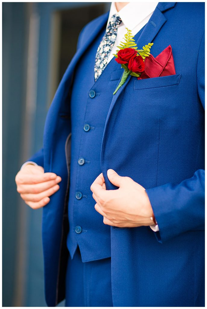 An image of a closeup view of the groom adjusting his bright blue tuxedo and vest, showing off his boutonniere at Dock 580 wedding venue  by Alayna Parker  - Columbus Ohio wedding images