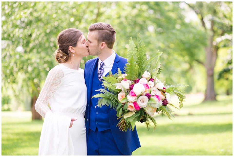 An image of a bride and groom tenderly kissing as they stand outdoors at Dock 580 wedding venue in downtown Columbus by Alayna Parker Photography  - Columbus Ohio wedding photographers