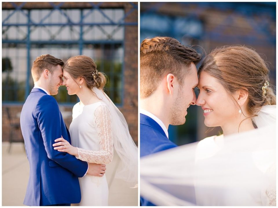 bride and groom touching foreheads with veil blowing across them
