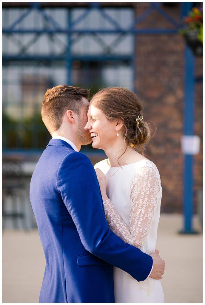bride laughing as groom whispers in her ear