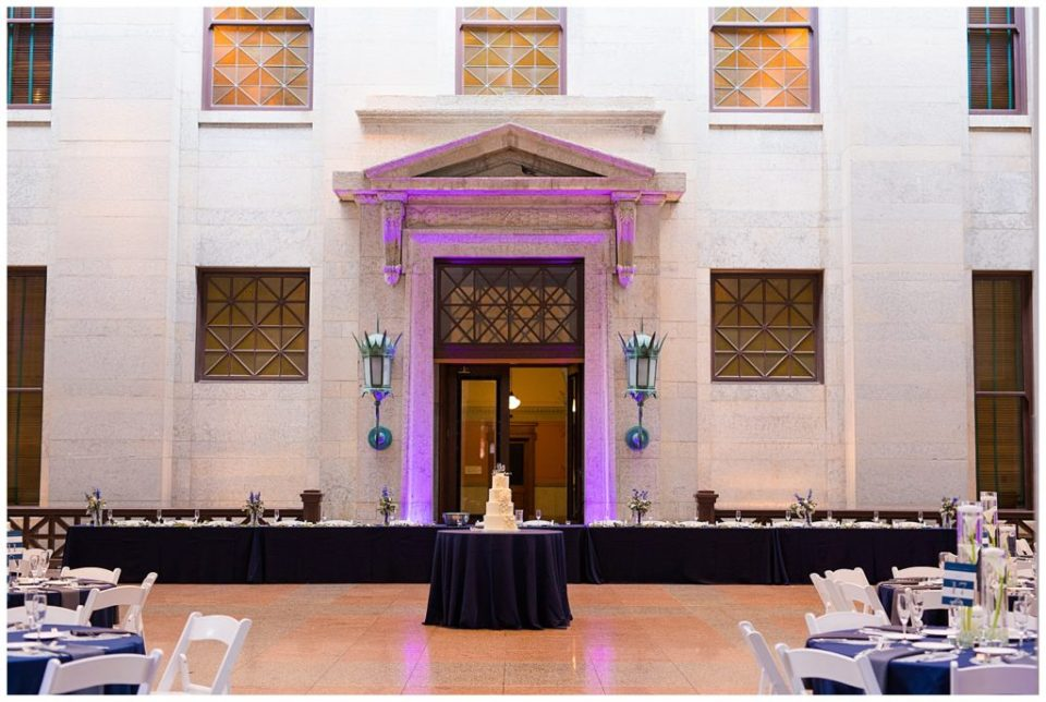 A picture of the head table decorated for the wedding party with the wedding cake featured on a table in front at the reception at the Ohio Statehouse by Alayna Parker  - Columbus  wedding photos