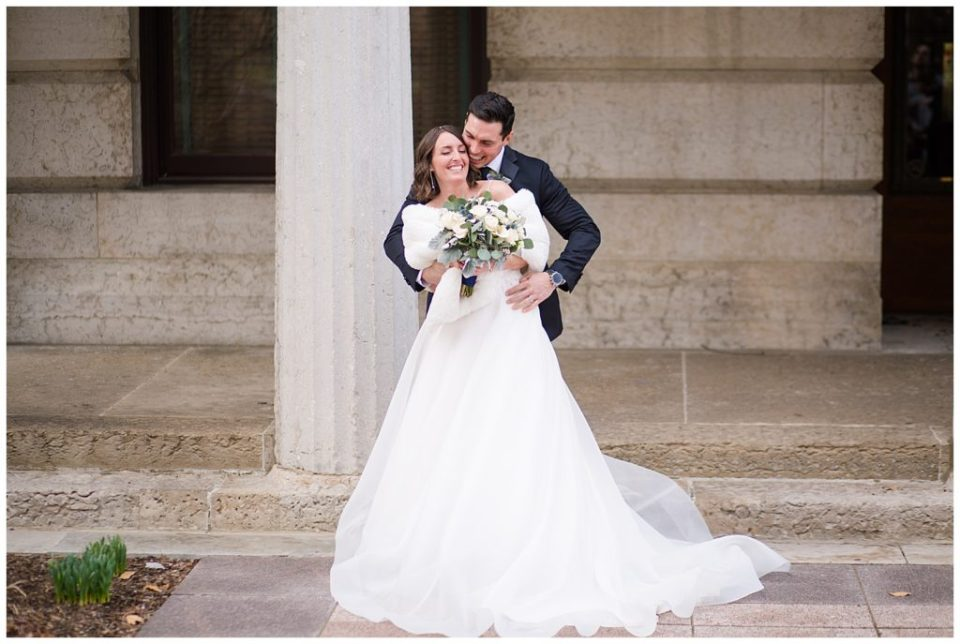 A photograph of a groom holding his bride as they smile and relax together, showing the bride's beautiful dress at an Ohio Statehouse wedding by Alayna Parker Photography  - Columbus OH wedding photographer