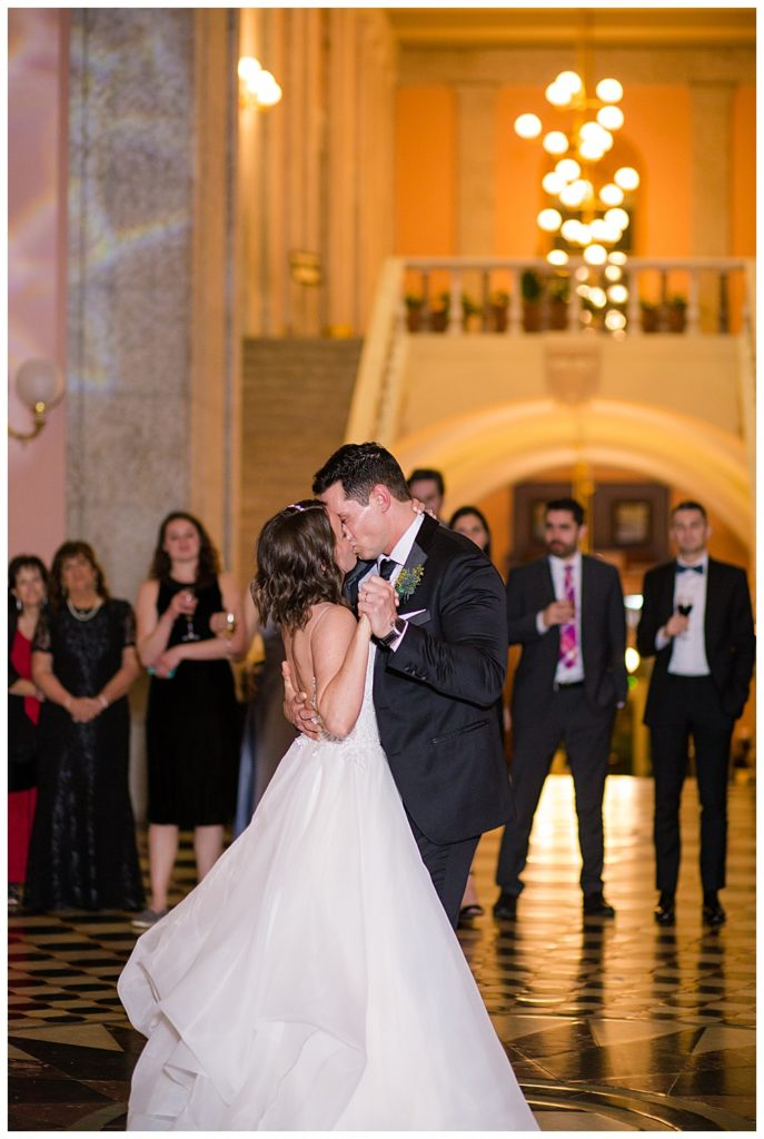 An image of a bride and groom romantically kissing as they have their first dance at the wedding reception at an Ohio Statehouse wedding by Alayna Parker Photography  - Columbus Ohio wedding photographers