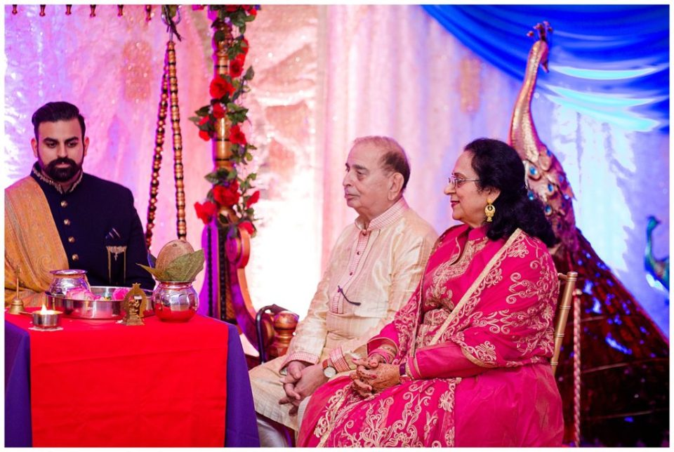 An image of a groom seated with his parents at a Hindu engagement ceremony at the Bertram Inn wedding venue by Alayna Parker  - Akron Ohio engagement photographer