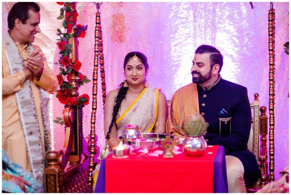 A photograph of the Hindu engaged couple smiling as they are seated at their engagement ceremony with the priest at the Bertram Inn wedding venue by Alayna Parker  - Akron OH engagement photography