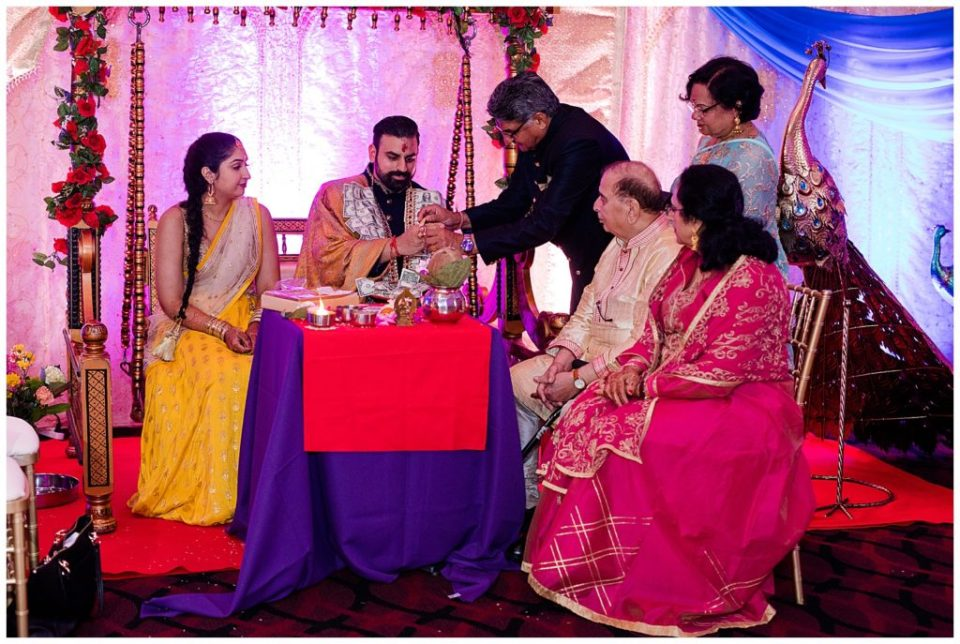 A photograph of an engaged couple sitting with family as they perform traditional Hindu rituals during their engagement ceremony at the Bertram Inn and Conference Center in Aurora by Alayna Parker  - Cleveland OH engagement photography