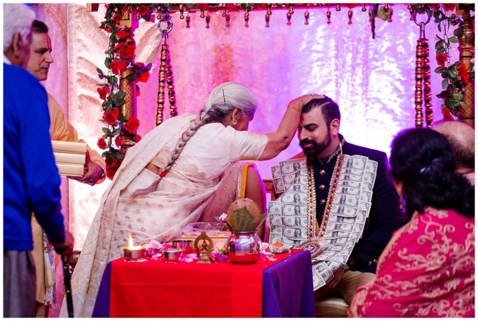 A picture of a Hindu groom blessed by a family member during their engagement celebration at the Bertram Inn wedding venue by Alayna Parker  - Akron  engagement photographers