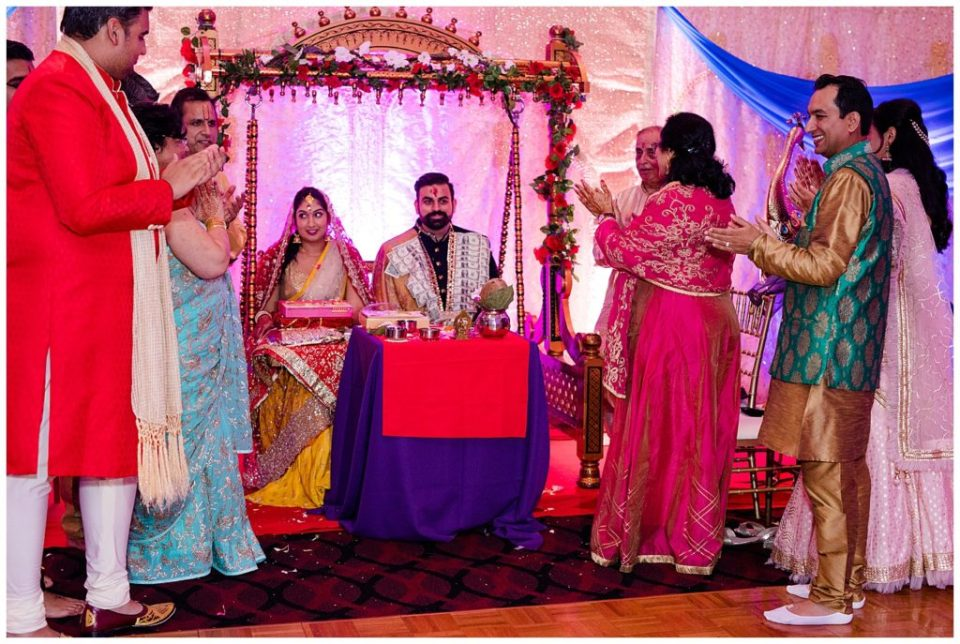 An image of a smiling engaged couple surrounded by family clapping as they conclude their Hindu engagement ceremony at the Bertram Inn wedding venue in Aurora, Ohio by Alayna Parker  - Cleveland Ohio engagement photographer