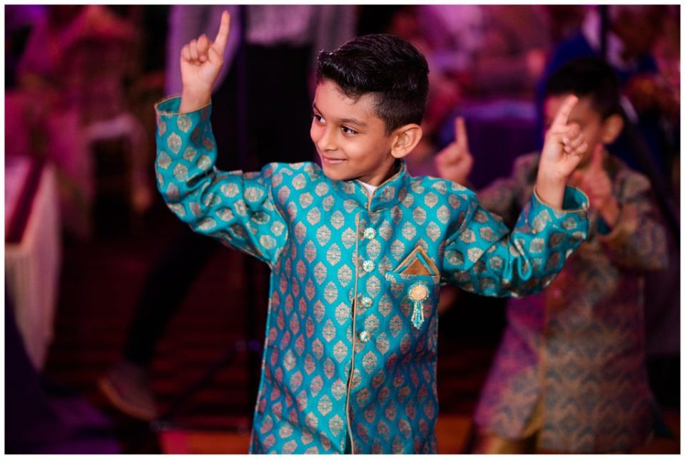 A photograph of a young Indian boy dancing and enjoying the celebrating at a Hindu engagement reception at the Bertram Inn wedding venue in Aurora, Ohio by Alayna Parker Photography  - Cleveland OH engagement photography
