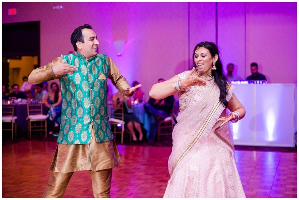 An image of two Indian dancers performing a traditional dance at a Hindu engagement celebration at the Bertram Inn wedding venue in Aurora, Ohio by Alayna Parker Photography  - Cleveland Ohio engagement photographer