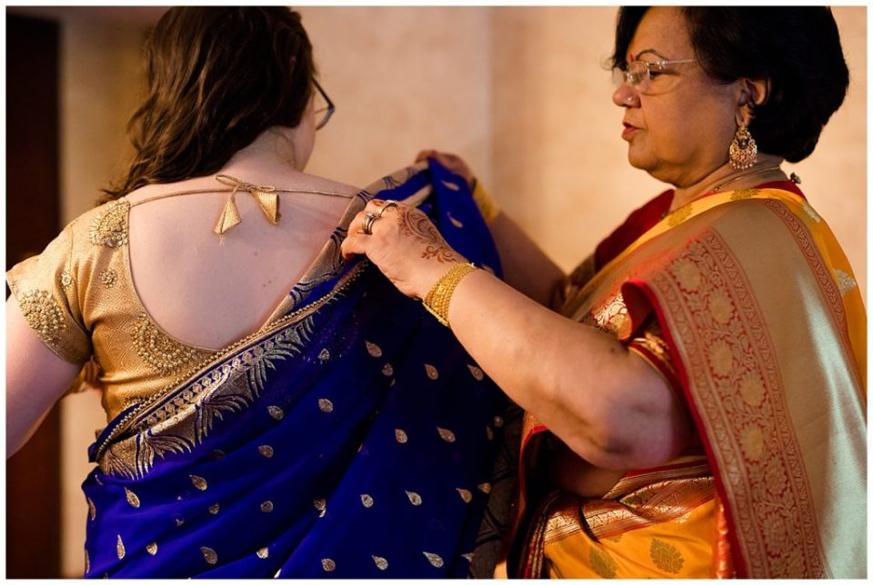 woman getting dressed in saree