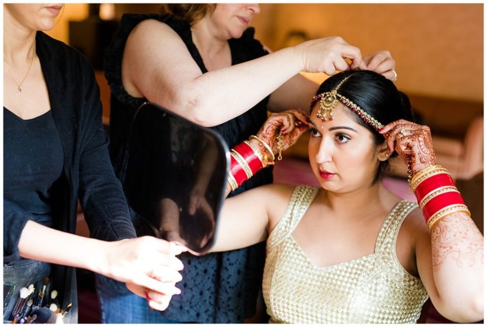 bride putting on indian headpiece