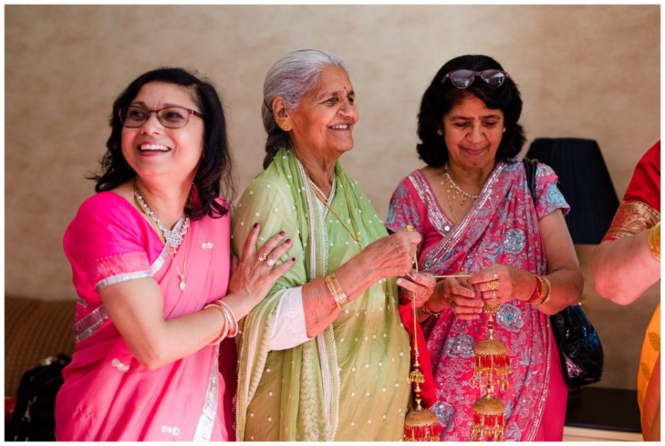 older indian women helping bride get dressed