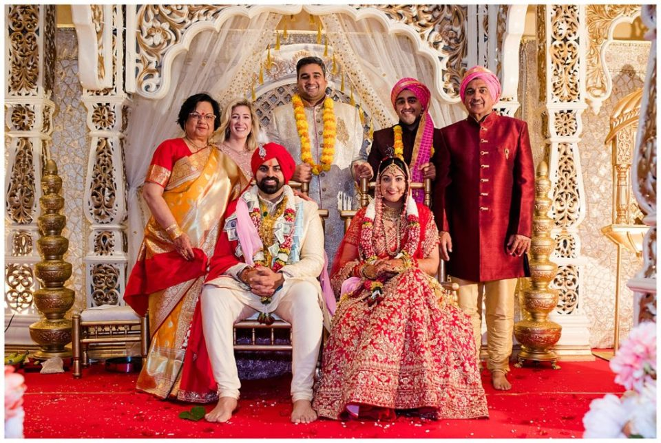 An image of an Indian bride and groom surrounded by the bride's family, smiling together in their beautiful clothes after the Hindu wedding at the Bertram Inn and Conference Center in Aurora by Alayna Parker  - Cleveland Ohio wedding photography