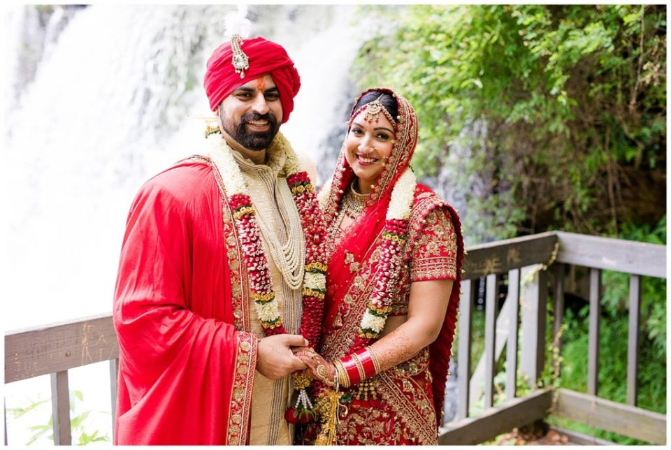 A photograph of a beautiful Indian bride and groom smiling and holding hands in their beautiful wedding clothes as they pause outdoors after the wedding in Chagrin Falls, OH by Alayna Parker  - Cleveland OH hindu wedding photographer