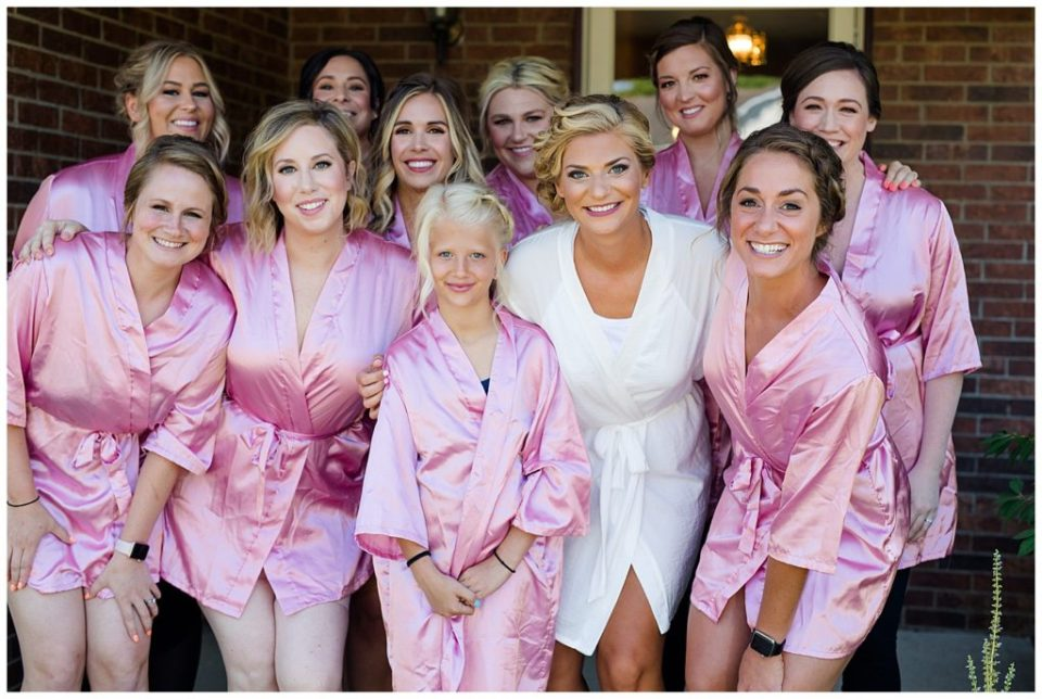 bride in white robe and bridesmaids in pink robes while getting ready