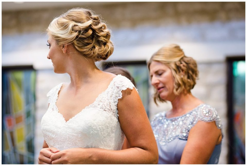 bride turning her head as she gets wedding dress on