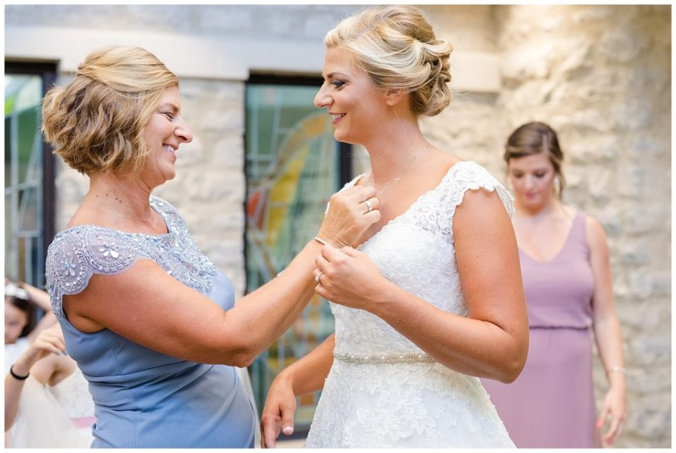 mother putting bride's necklace on