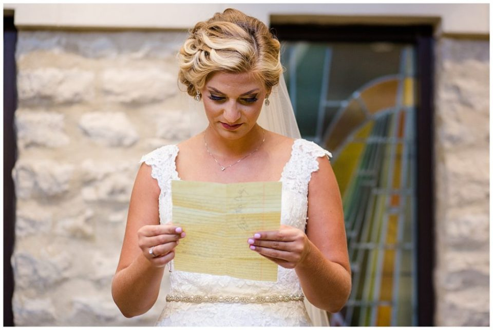 An image of the bride reading over her grooms letter just before the wedding ceremony at the St Andrew church in Columbus by Alayna Parker  - Columbus Ohio wedding photographers