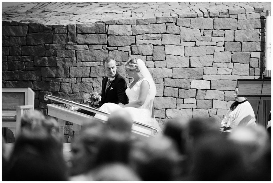 An image in black and white of the bride and groom seated to the side of the stage, smiling at each other, as the ceremony proceeds at the St Andrew church in Columbus by Alayna Parker  -   wedding photographers in Columbus Ohio