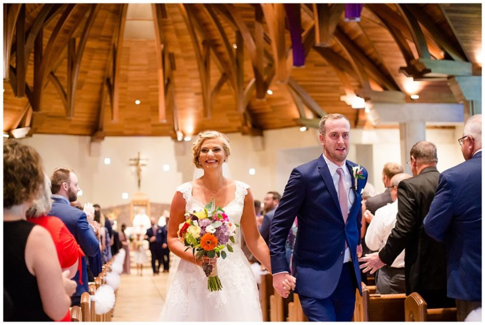 A picture of the bride and groom walking down the aisle, holding hands and smiling after their wedding ceremony  by Alayna Parker  - Columbus  wedding photographers
