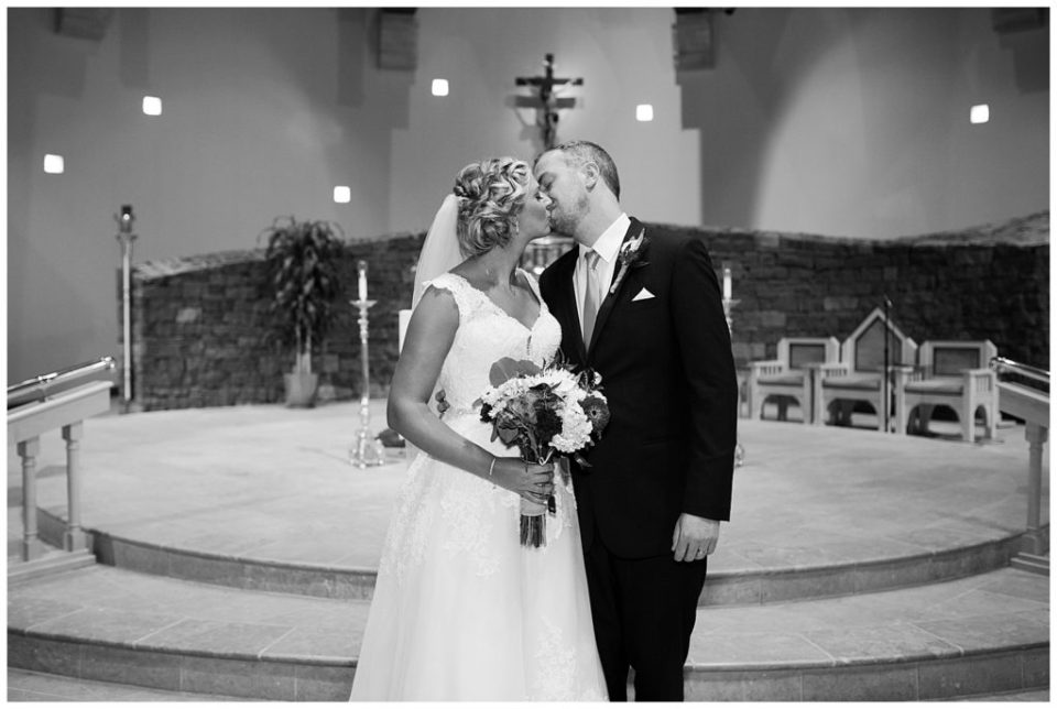 A photograph in black and white of the bride and groom kissing in the church shortly after the wedding ceremony  by Alayna Parker Photography  - Columbus OH wedding photographer