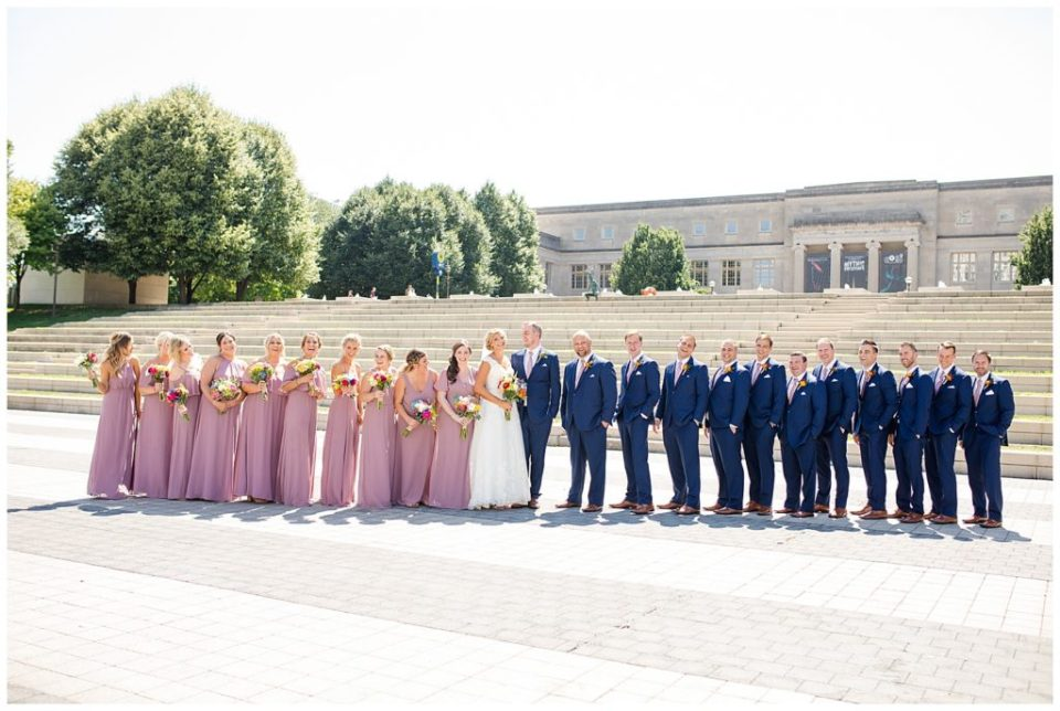 A picture of a long-range view of the wedding party outside, lined up and smiling together at COSI in Columbus by Alayna Parker Photography  - Columbus  wedding photography