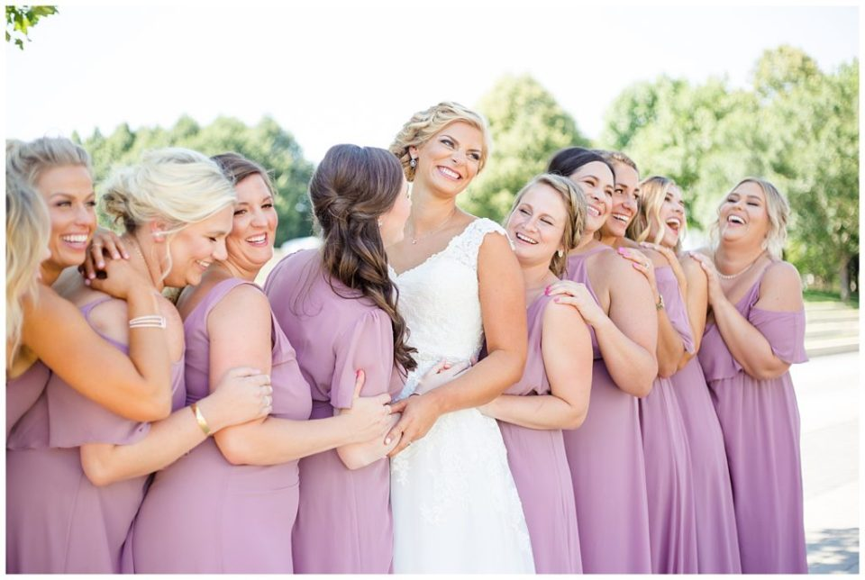 A picture of the bride lined up with her bridesmaids, smiling and laughing together at COSI in Columbus by Alayna Parker Photography  -   wedding photographer in Columbus