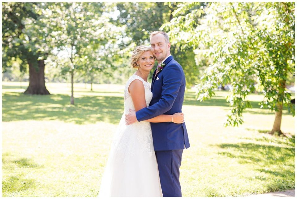 A picture of the bride and groom holding each other close, smiling in a beautiful sunny park setting in Schiller Park in Columbus by Alayna Parker Photography  -   wedding photographers in Columbus Ohio