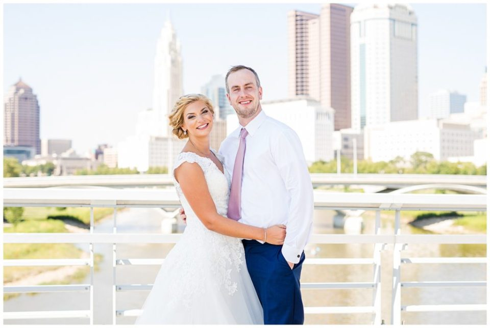 bride and groom smiling at camera with columbus skyline in background