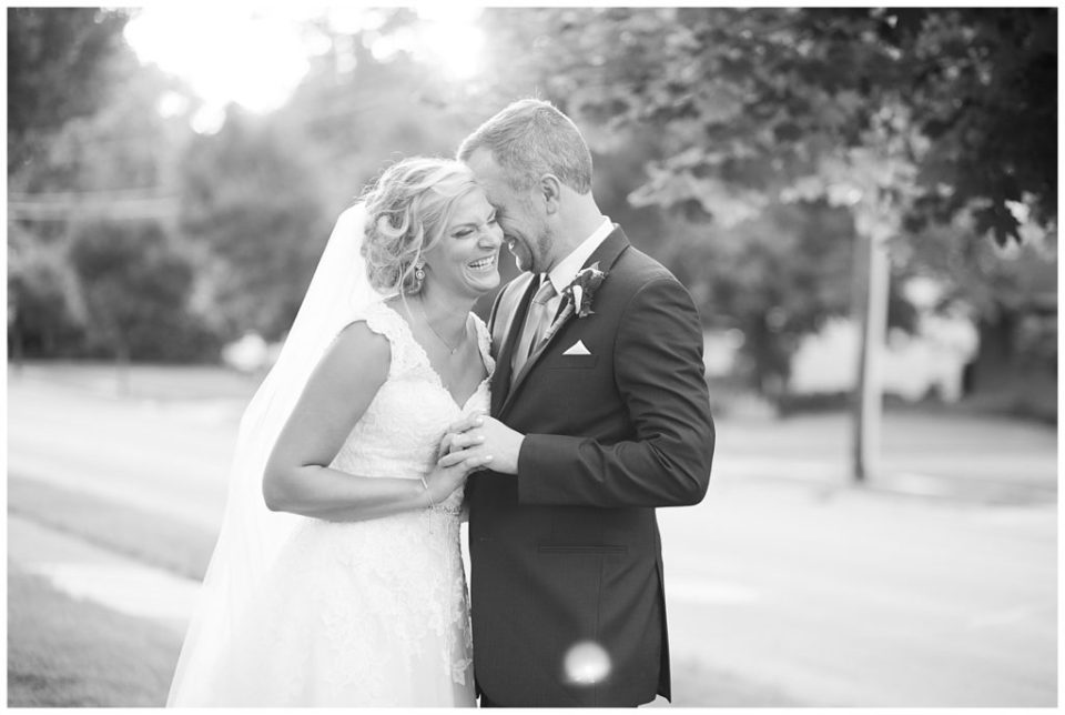black and white image of bride laughing while groom nuzzles into her