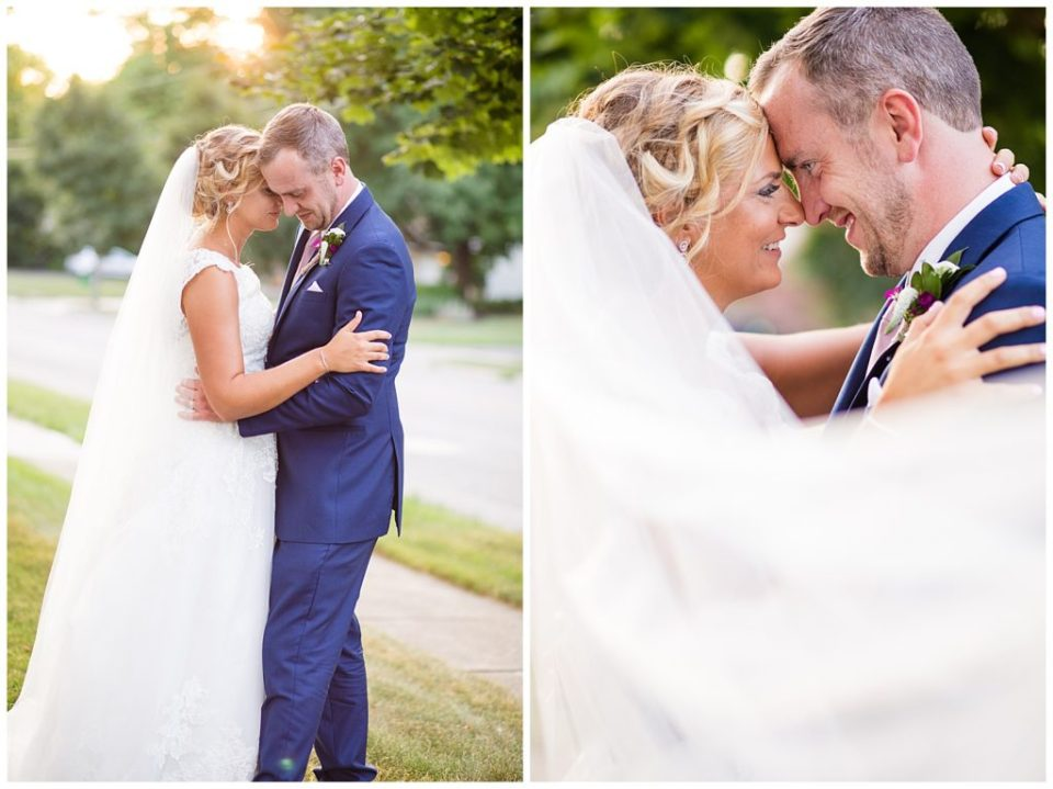 bride and groom touching foreheads while veil blows in wind
