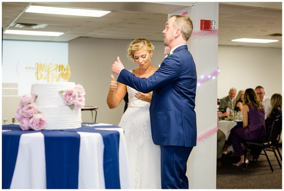 bride and groom give thumbs up after eating cake