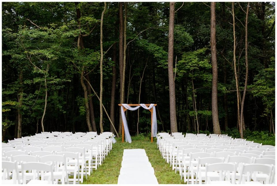 An image of a rustic outdoor wedding arch draped in a chiffon scarf with a background of trees with white chairs set up for guests at the Cedar Grove Lodge wedding venue by Columbus Ohio wedding photographer, Alayna Parker Photography