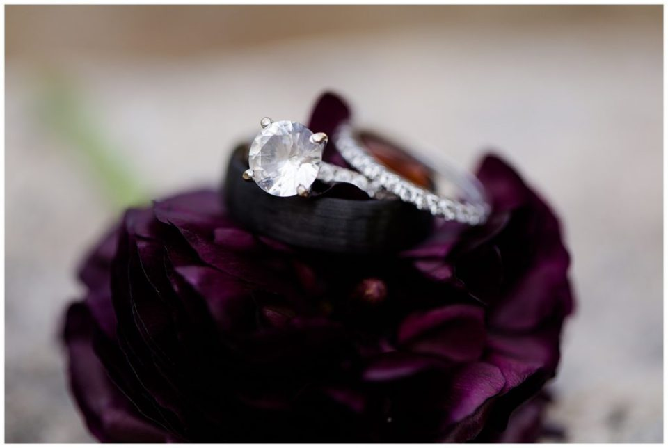 A photograph of a closeup look at the wedding rings atop a beautiful flower at the Cedar Grove Lodge wedding venue by Columbus OH wedding photographer, Alayna Parker Photography