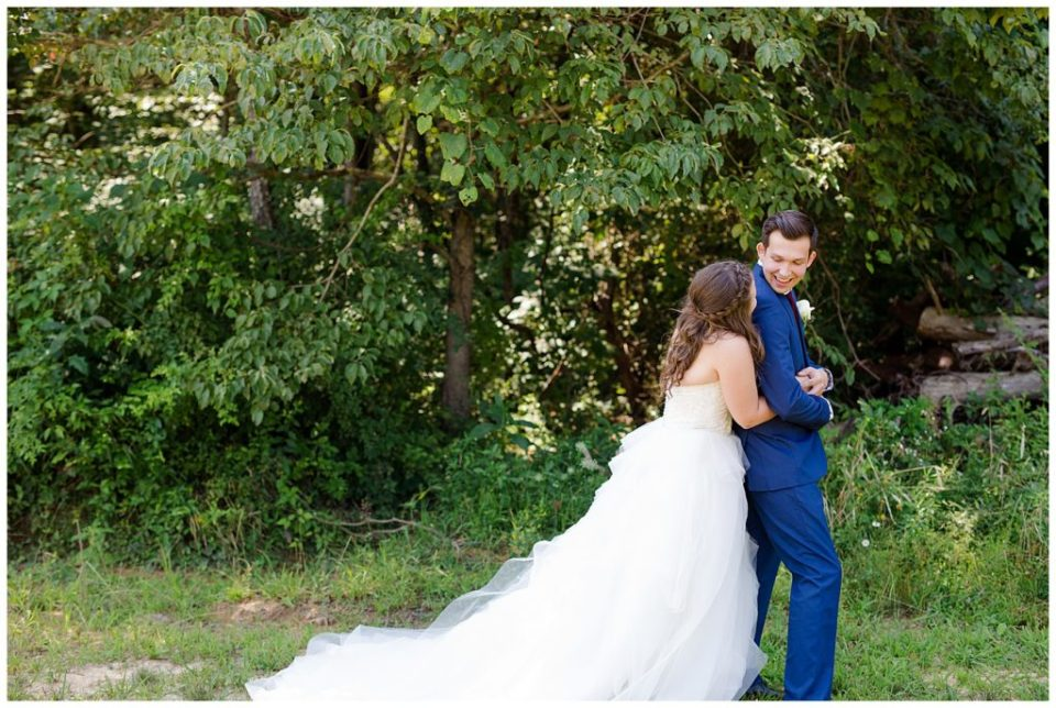 A photograph of the bride approaching her groom from behind for the first look before the wedding at the Cedar Grove Lodge venue in Hocking Hills, Ohio by Columbus OH wedding photographer, Alayna Parker Photography