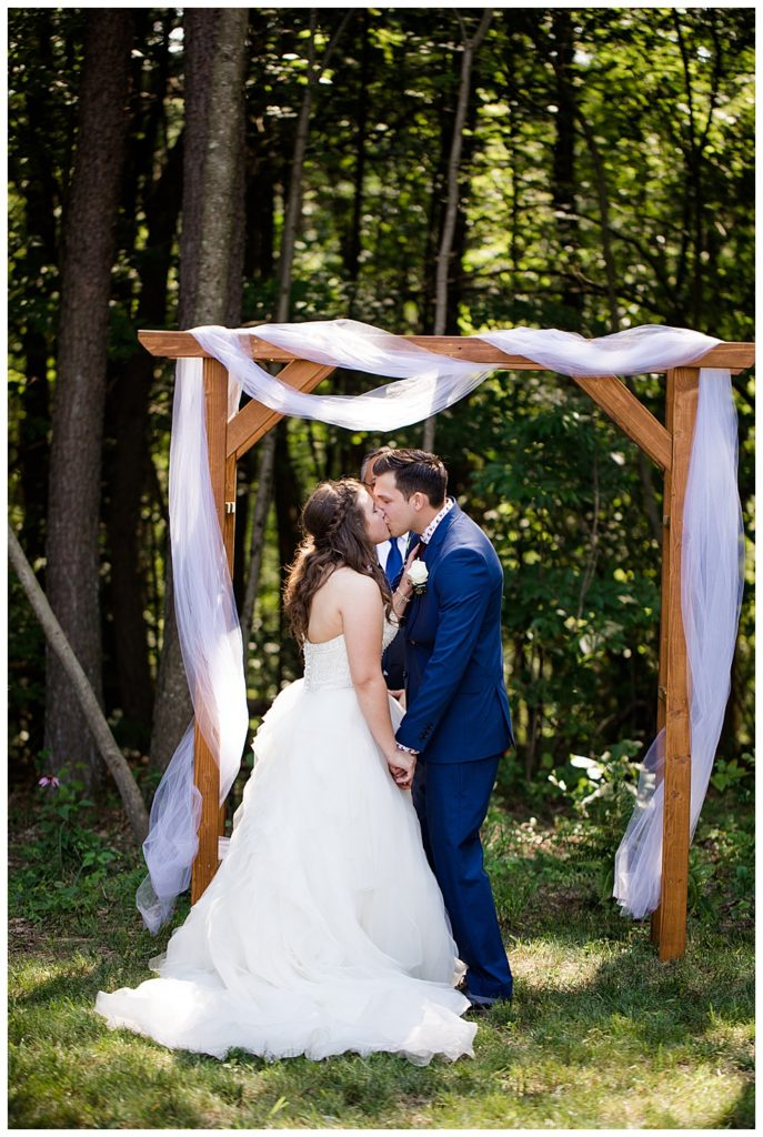 An image of the bride and groom kissing at the end of the wedding ceremony, framed by a rustic arch and trees at the Cedar Grove Lodge venue in Hocking Hills, Ohio by Columbus Ohio wedding photographer, Alayna Parker Photography
