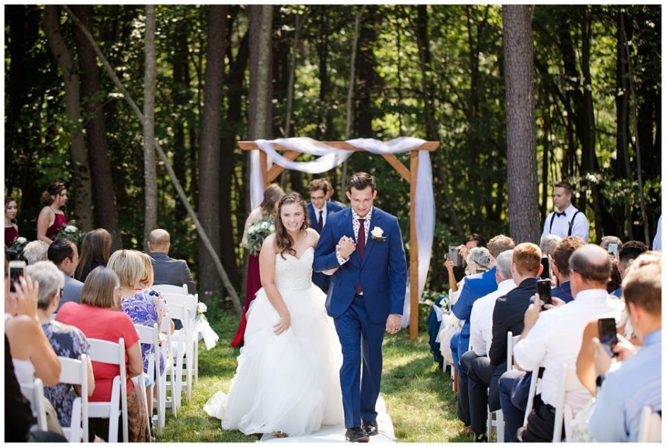 A photograph of the bride and groom smiling and walking down the aisle just after the wedding ceremony as the guests look on at the Cedar Grove Lodge wedding venue by Columbus OH wedding photographer, Alayna Parker Photography