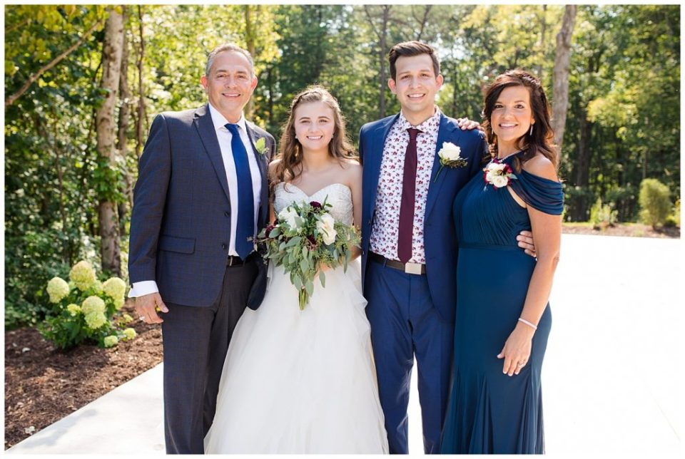 A picture of the bride and groom smiling with their parents after the wedding at the Cedar Grove Lodge venue in Hocking Hills, Ohio by Columbus  wedding photographer, Alayna Parker Photography