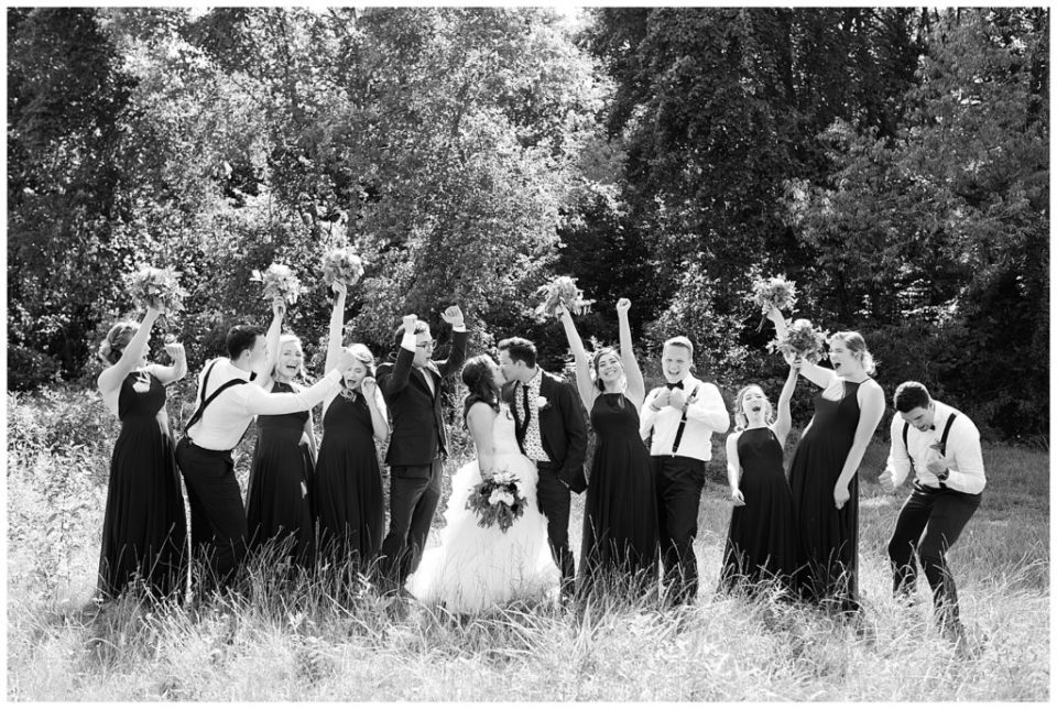 black and white image of bridal party cheering while bride and groom kiss in field at cedar grove lodge