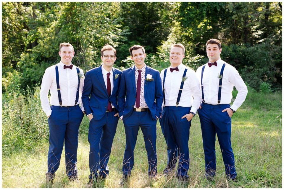 groomsmen wearing white shirt, blue suit pants, and suspenders and smiling at camera