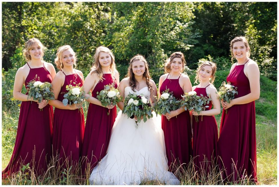 bridesmaids wearing long burgundy dresses and smiling at camera