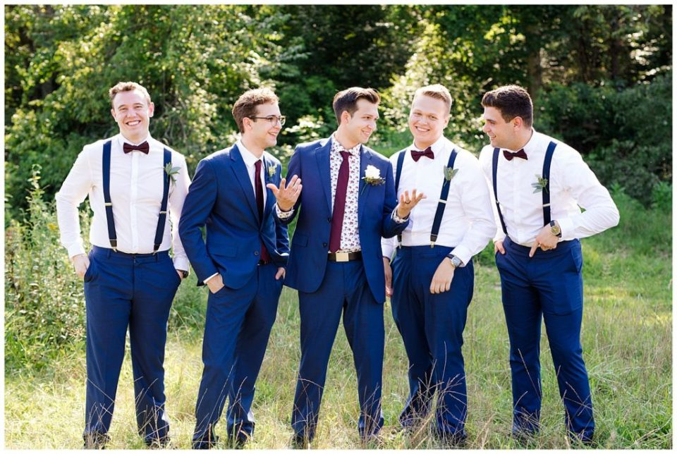 groom and groomsmen laughing and talking in field at cedar grove lodge