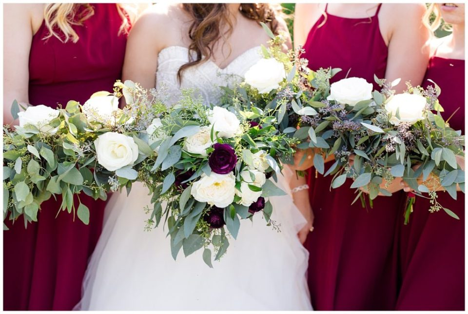 close up of bride and bridesmaids holding bouquets of eucalyptus, white flowers, and dark purple flowers