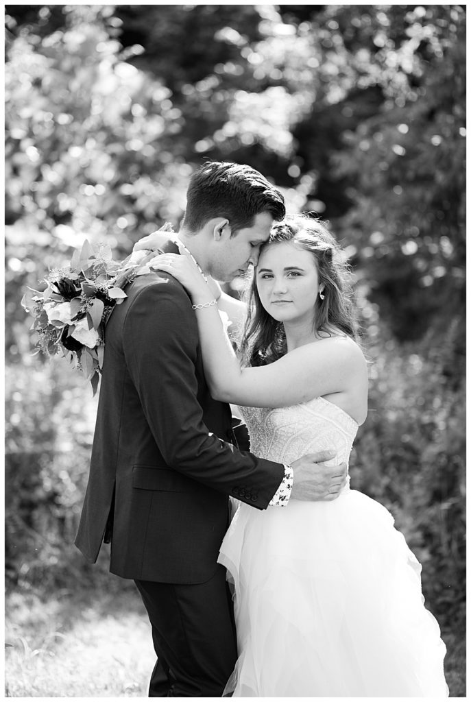 black and white image of bride looking at camera while groom nuzzles into her