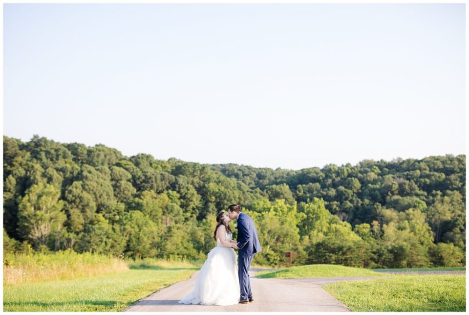 bride and groom kissing on top of hill overlooking trees at cedar grove lodge