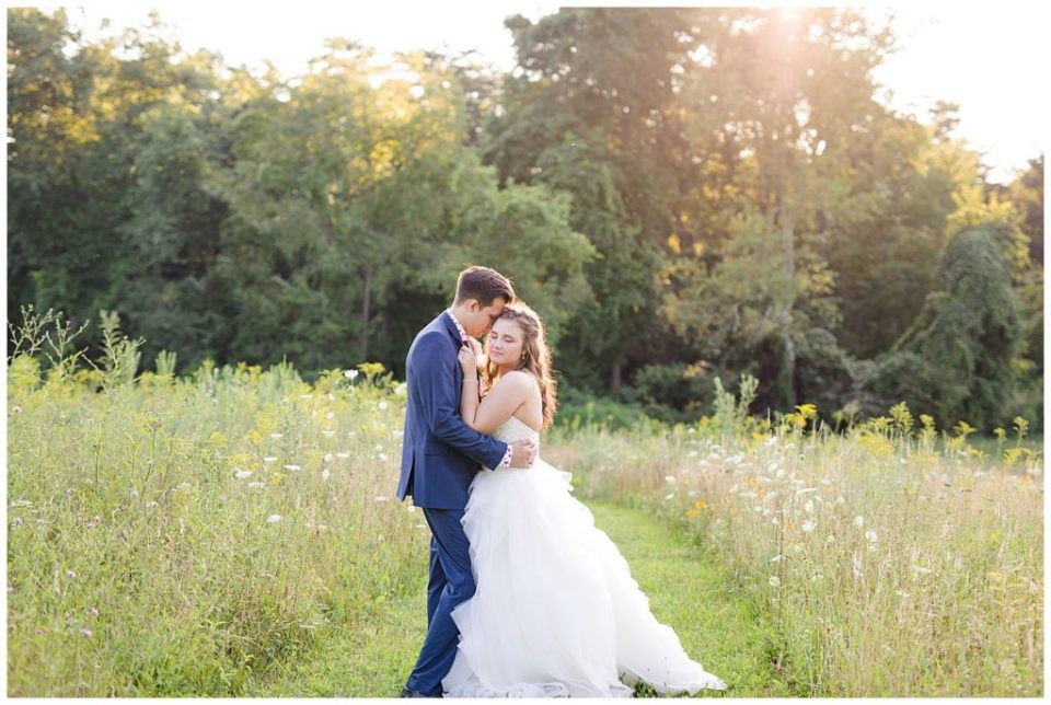 bride closing her eyes and groom holding onto her in field at golden hour at cedar grove lodge